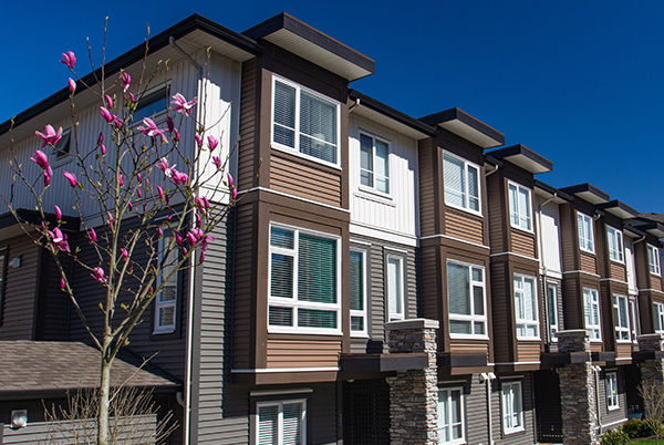 Brand new apartment building on sunny day in spring with blooming trees.